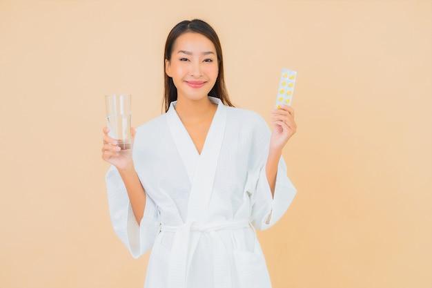 Porträt schöne junge asiatische frau mit wasserglas und drogenpille auf beige