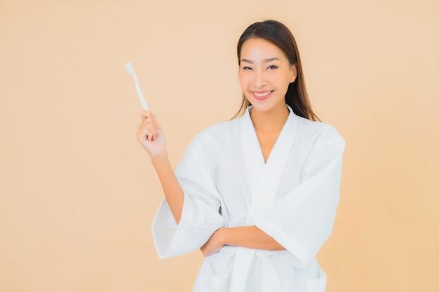 Porträt schöne junge asiatische frau mit zahnbürste auf beige