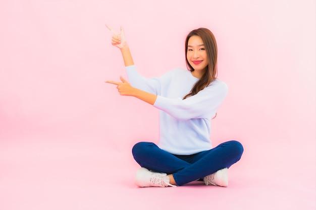 Porträt schöne junge asiatische frau sitzen auf boden mit rosa farbe isolierte wand