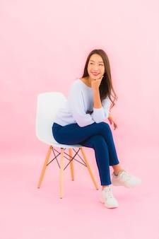 Porträt schöne junge asiatische frau sitzen auf stuhl mit rosa farbe wand