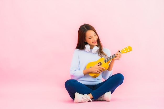 Porträt schöne junge asiatische frau spielen ukulele auf rosa farbe isolierte wand