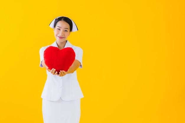 Porträt schöne junge asiatische frau thailändische krankenschwester mit herzkissenform