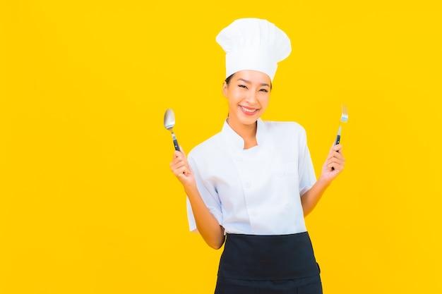 Porträt schöne junge asiatische frau trägt koch oder kochuniform mit löffel und gabel auf gelb isoliertem hintergrund