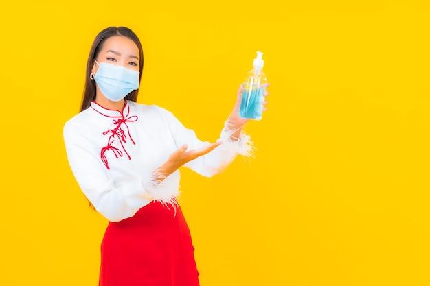 Porträt schöne junge asiatische frau trägt maske und verwendet alkoholgel zum schutz von covid19 auf gelb