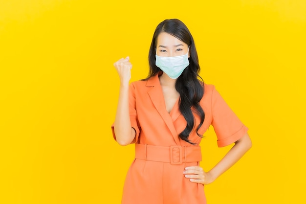 Porträt schöne junge asiatische frau tragen maske zum schutz covid19 auf gelb