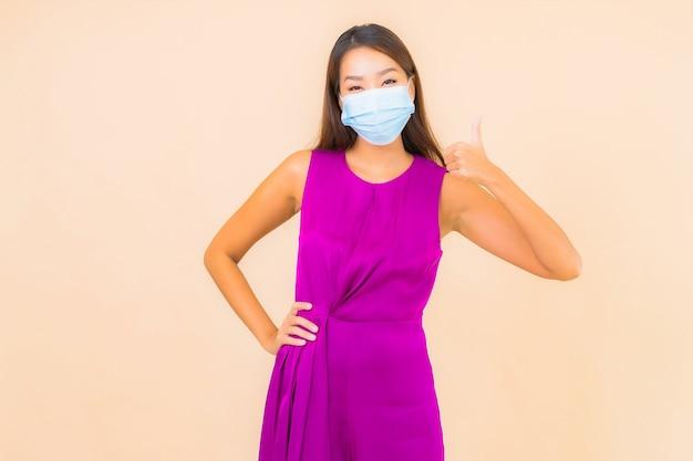 Porträt schöne junge asiatische frau tragen maske zum schutz vor covid19 oder corona-virus auf farbhintergrund