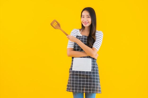 Porträt schöne junge asiatische frau tragen schürze mit schwarzer pfanne und spatel