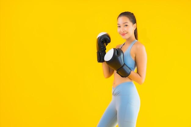 Porträt schöne junge asiatische frau tragen sportbekleidung auf gelb
