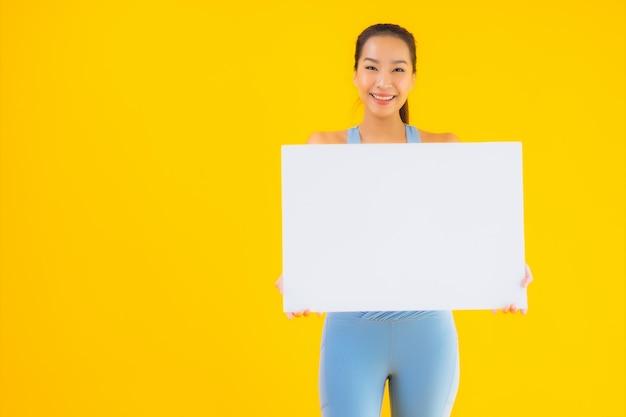Porträt schöne junge asiatische frau tragen sportbekleidung zeigen leere weiße werbetafel auf gelb