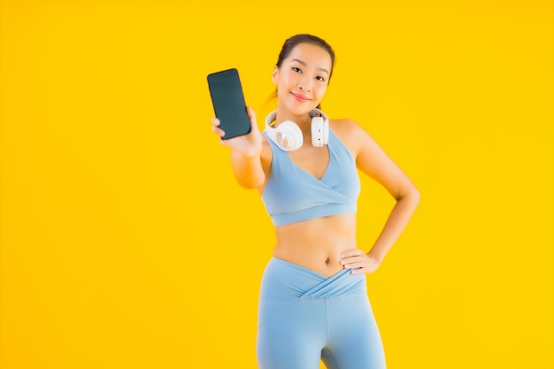 Porträt schöne junge asiatische frau tragen sportkleidung mit smartphone