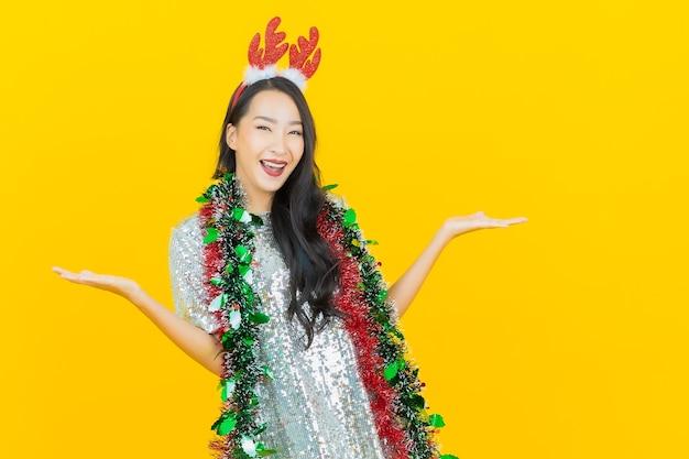 Porträt schöne junge asiatische frau tragen weihnachtsoutfit auf gelb