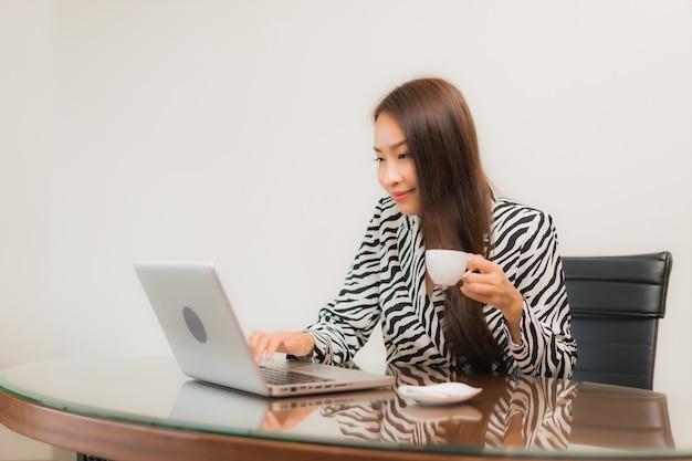Porträt schöne junge asiatische frau verwenden computer laptop auf arbeitstisch im raum
