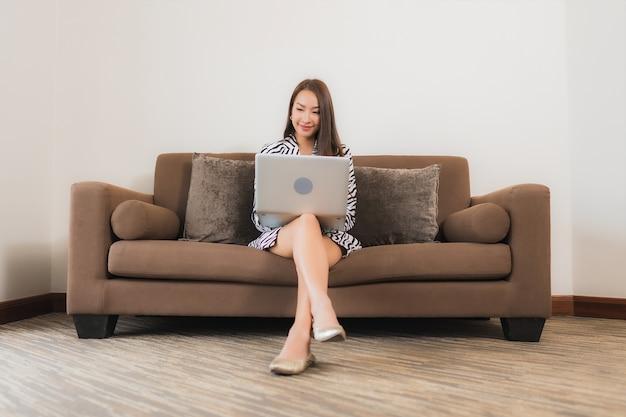 Porträt schöne junge asiatische frau verwenden computer laptop auf sofa im wohnzimmer innenbereich