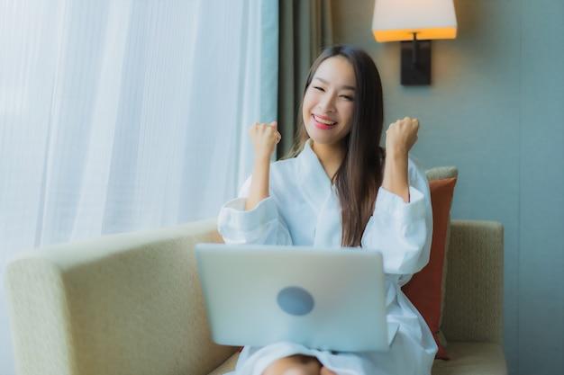 Porträt schöne junge asiatische frau verwenden computer laptop auf sofa im wohnzimmerbereich
