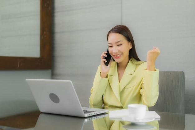 Porträt schöne junge asiatische frau verwenden computer-laptop mit smart-handy auf arbeitstisch im innenraum