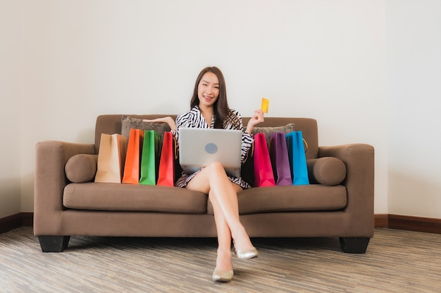Porträt schöne junge asiatische frau verwenden computer-laptop, smartphone oder bargeld für online-shopping auf sofa im wohnzimmer interieur