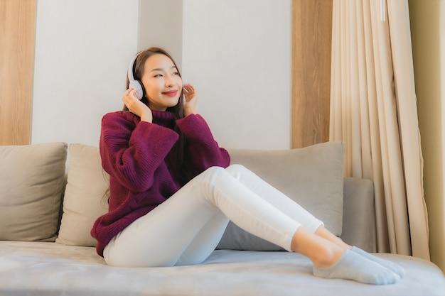 Porträt schöne junge asiatische frau verwenden kopfhörer für musik auf sofa im wohnzimmer interieur zu hören