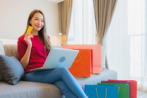 Porträt schöne junge asiatische frau verwenden laptop-computer mit kreditkarte