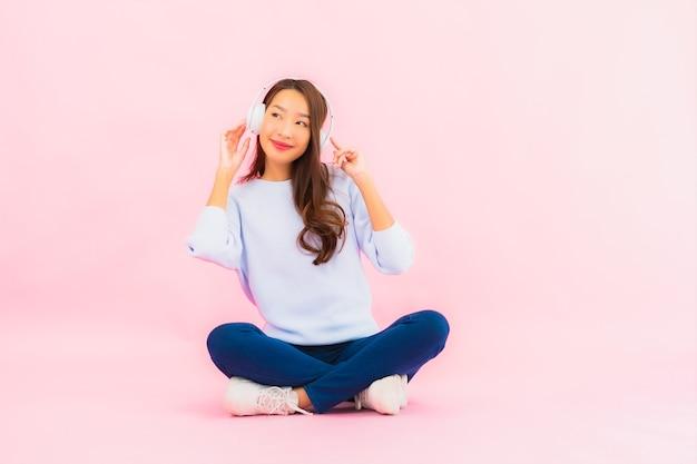 Porträt schöne junge asiatische frau verwenden smart-handy mit kopfhörer für musik auf rosa wand zu hören