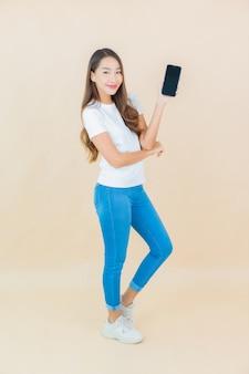 Porträt schöne junge asiatische frau verwenden smartphone auf beige