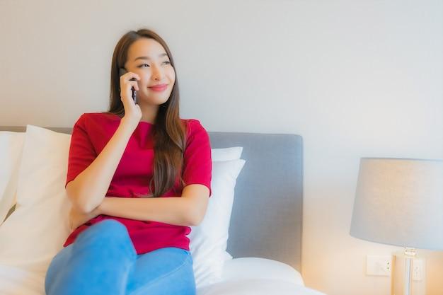 Porträt schöne junge asiatische frau verwenden smartphone auf dem bett