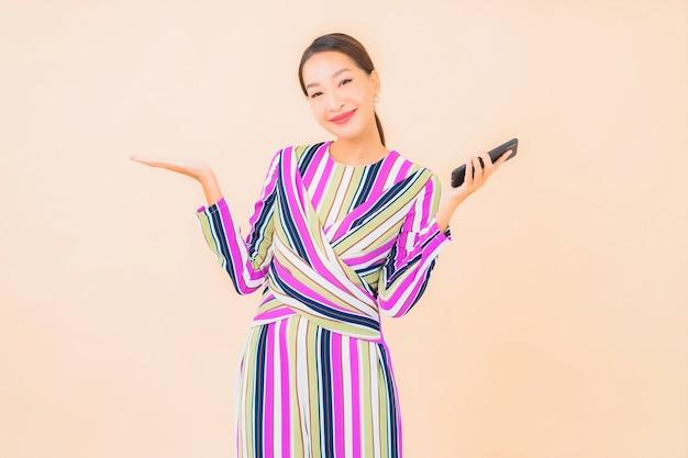 Porträt schöne junge asiatische frau verwenden smartphone auf farbe