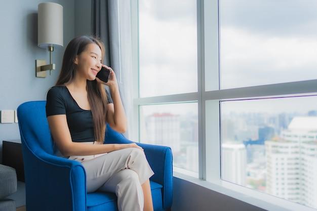 Porträt schöne junge asiatische frau verwenden smartphone auf sofa im wohnzimmerbereich