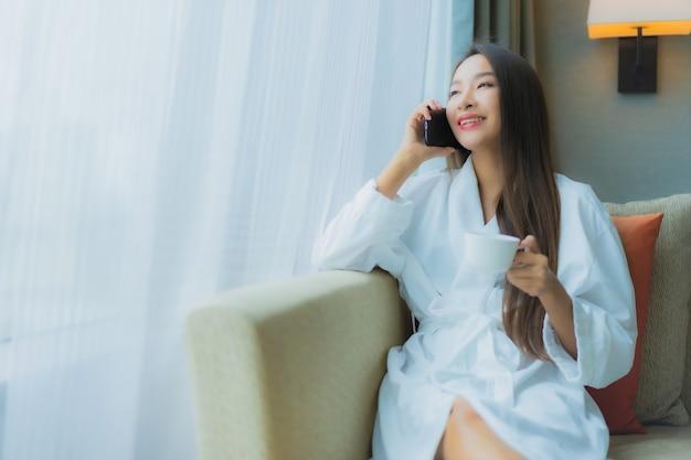 Porträt schöne junge asiatische frau verwenden smartphone auf sofa