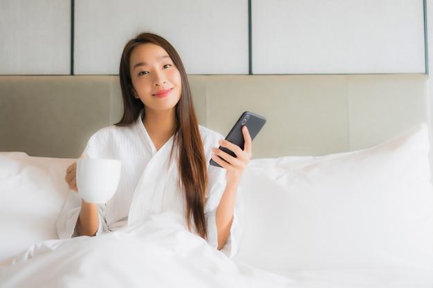 Porträt schöne junge asiatische frau verwenden smartphone im schlafzimmer