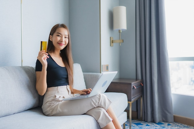 Porträt schöne junge asiatische frau verwenden smartphone oder laptop mit kreditkarte auf sofa im wohnzimmerbereich