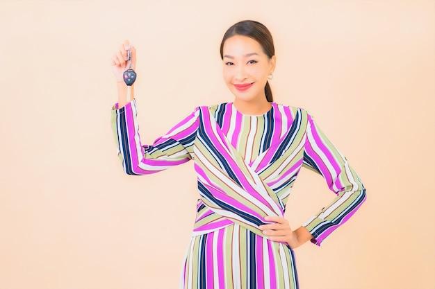 Porträt schöne junge asiatische frau zeigen autoschlüssel auf farbe