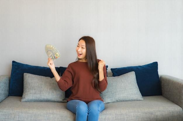 Porträt schöne junge asiatische frau zeigen geld und geld auf sofa im wohnzimmer interieur