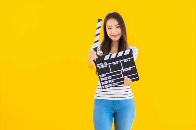 Porträt schöne junge asiatische frau zeigen klöppel filmbrett