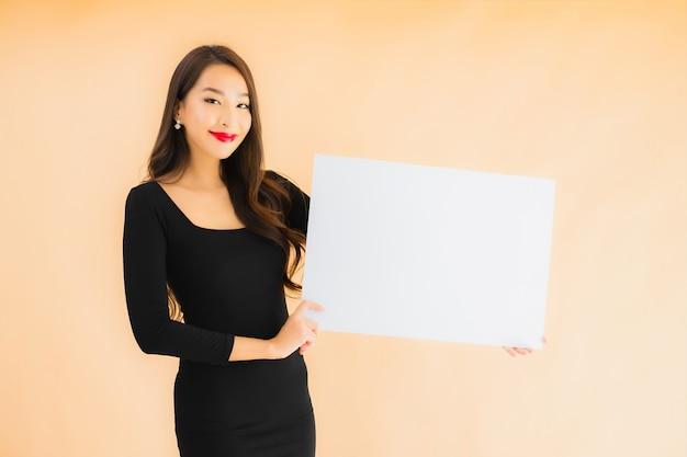 Porträt schöne junge asiatische frau zeigen leere weiße tafel