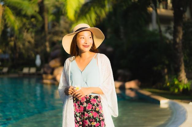 Porträt schöne junge asiatische frauen glückliches lächeln entspannen um schwimmbad