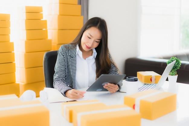 Porträt schöne junge asiatische geschäftsfrau arbeit von zu hause mit laptop-handy mit pappkarton bereit für den versand