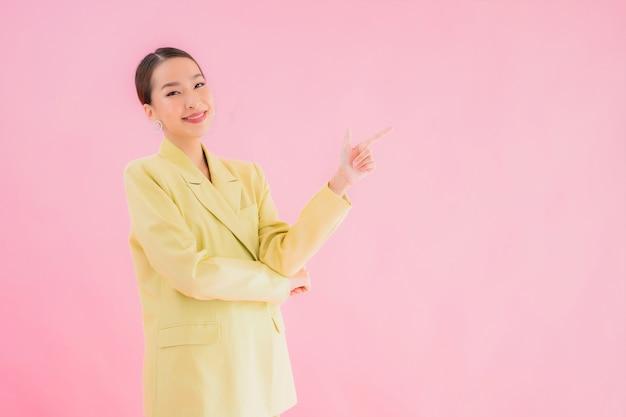 Porträt schöne junge asiatische geschäftsfrau lächeln in aktion auf rosa farbe