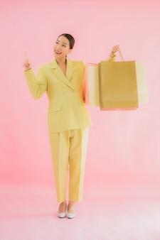 Porträt schöne junge asiatische geschäftsfrau mit einkaufstasche auf farbe lokalisiert