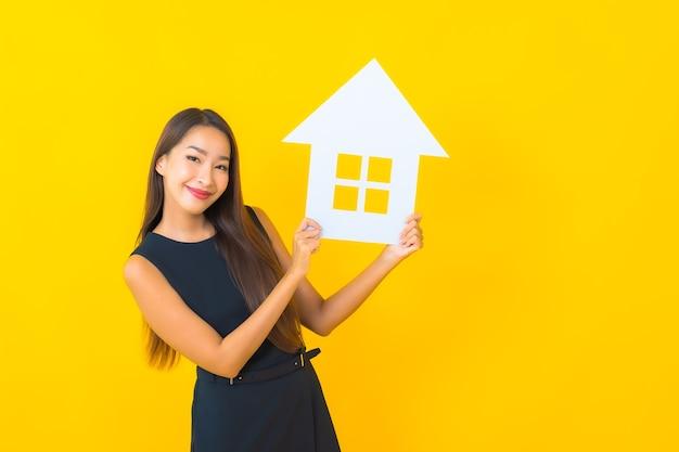 Porträt schöne junge asiatische geschäftsfrau mit hauspapierschild auf gelbem hintergrund