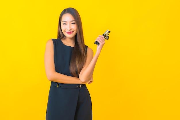 Porträt schöne junge asiatische geschäftsfrau mit make-up-kosmetikpinsel auf gelbem hintergrund