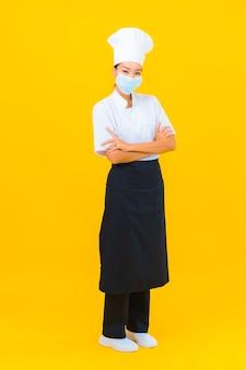 Porträt schöne junge asiatische köchin tragen maske zum schutz von covid19 oder coronavirus auf gelbem, isoliertem hintergrund