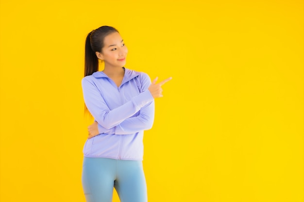 Porträt schöne junge asiatische sportfrau bereit für übung auf gelb