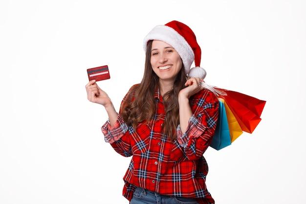 Porträt schöne junge frau, die weihnachtsweihnachtsmütze mit einkaufstaschen und kreditkarte trägt