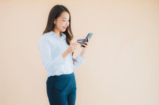 Porträt schöne junge geschäftsasiatin mit telefon und kreditkarte