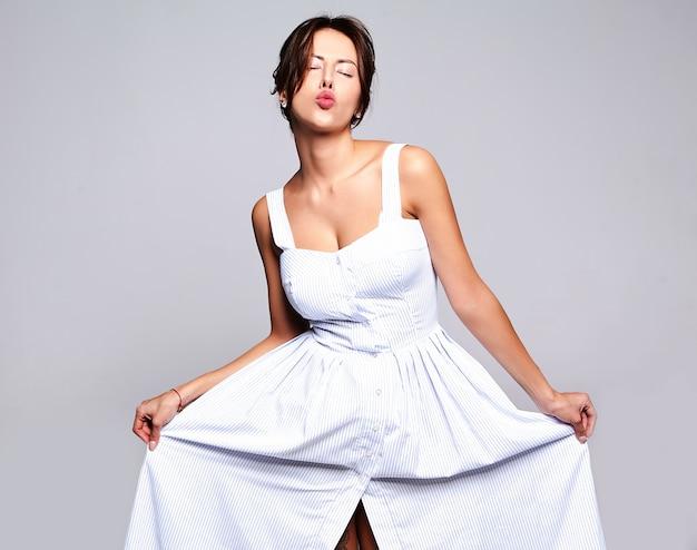 Porträt schöne niedliche brünette frau modell in lässigen sommerkleid ohne make-up auf grau isoliert. einen kuss geben