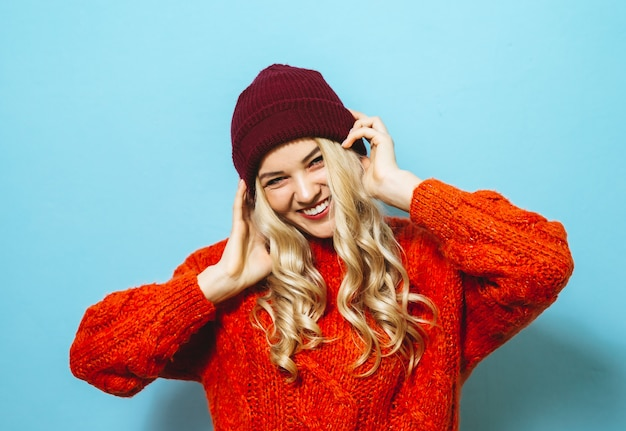 Porträt schönen blondine, die eine kappe tragen und in einer roten strickjacke gekleidet werden und mode zeigen, bewegt sich über blauen hintergrund