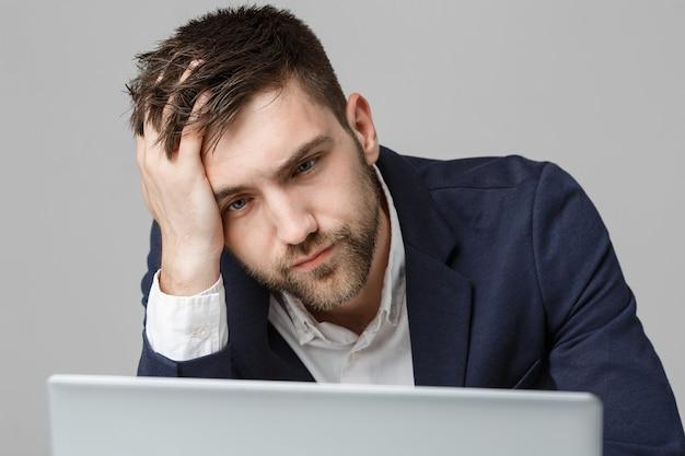 Porträt schöner hübscher geschäftsmann im anzug, der laptop betrachtet
