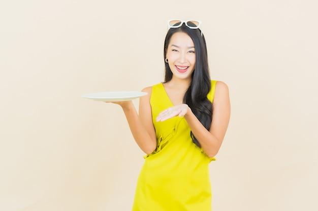 Porträt schönes junges asiatisches frauenlächeln mit leerem tellergericht auf farbwand