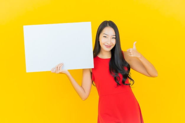Porträt schönes junges asiatisches frauenlächeln mit leerer weißer plakatwand auf gelber wand