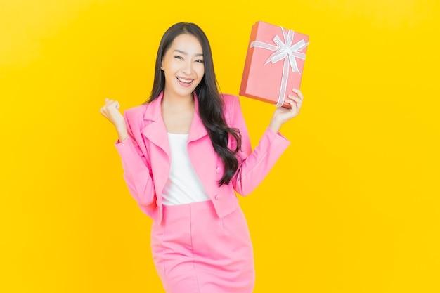 Porträt schönes junges asiatisches frauenlächeln mit roter geschenkbox auf gelber farbwand color